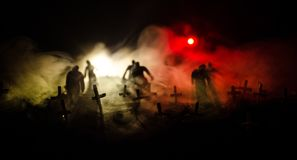 Silhouette of zombies walking over cemetery in night. Horror Halloween concept of group of zombies at night Stock Photo