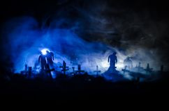 Silhouette of zombies walking over cemetery in night. Horror Halloween concept of group of zombies at night Stock Image