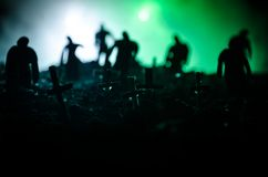 Silhouette of zombies walking over cemetery in night. Horror Halloween concept of group of zombies at night Royalty Free Stock Images