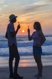 Silhouetted восход солнца пляжа друзей Стоковая Фотография