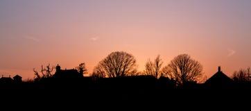 Silhouetted горизонт деревни на сумраке Стоковые Изображения