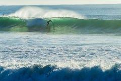 Silhouetted езда волны серфера Стоковые Фото