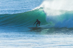 Silhouetted езда волны серфера Стоковая Фотография