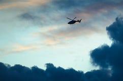 Silhouetted летание вертолета через небо захода солнца Стоковое Изображение RF
