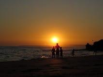 Silhouetted дети на @Beach захода солнца стоковые фотографии rf