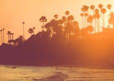 Silhouetted люди на пляже на заходе солнца Стоковые Фотографии RF
