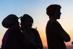 Silhouetted мальчик беседы девушек Стоковое Изображение RF