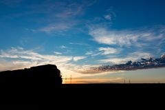 Silhouetted поезд на заходе солнца на канадской прерии Стоковые Фотографии RF