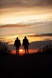 2 silhouetted старшия идя в заход солнца Стоковое Изображение RF