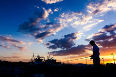 Silhouetted съемка рыбной ловли мальчика на пристани на заходе солнца Стоковая Фотография