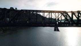 Silhouetted Aerial Cargo Train on Railroad Bridge. 9272 A silhouetted aerial shot of a cargo train traveling over a railroad bridge spanning the Ohio River stock footage