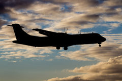 Silhouetted aircraft in flight Stock Photos