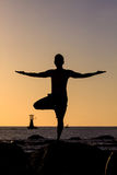 Silhouetted of asian man acts yoga Stock Photos