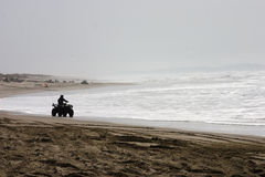 Silhouetted ATV rider on the Beach royalty free stock image