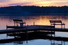Silhouetted Benches on Wooden Pier at Sunset. Wood and metal benches on wooden pier are silhouetted against glittering waters of McCullom Lake, McHenry, IL as royalty free stock images