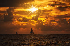 Silhouetted boat gainst a vivid colorful sunset Stock Photo