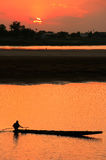 Silhouetted boat on Mekong river at sunset. Vientiane, Laos, Southeast Asia Royalty Free Stock Photo