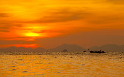 Silhouetted of boat in the sea at Krabi, Thailand. Stock Photos