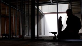 Silhouetted builder prepares to drill on construction site stock video footage