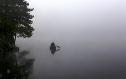 Silhouetted Canoer. A silhouetted canoer paddling on a still lake in Algonquin Provincial Park, in Ontario, Canada Royalty Free Stock Images