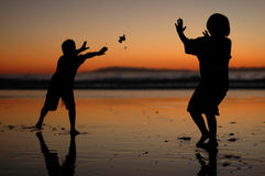 Silhouetted Children Playing on the Beach Stock Photo