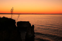 Silhouetted cliffs at sunrise, Ponta de Piedade, Lagos, Algarve, Royalty Free Stock Images