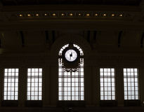 Silhouetted clock and windows of historic train station Royalty Free Stock Photography