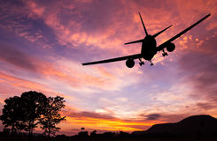 Silhouetted commercial airplane flying Stock Photos