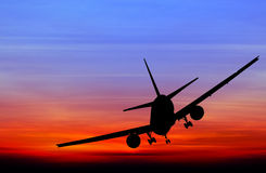 Silhouetted commercial airplane flying Stock Images