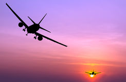 Silhouetted commercial airplane flying Royalty Free Stock Image