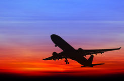 Silhouetted commercial airplane flying Royalty Free Stock Photos