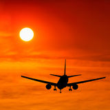 Silhouetted commercial airplane flying Royalty Free Stock Photography