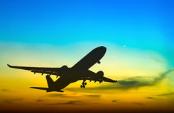 Silhouetted commercial airplane flying Stock Photo