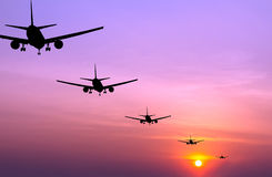 Silhouetted commercial airplane flying Stock Photography
