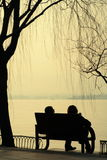 Silhouetted couple sat by lake. Rear view silhouette of couple sat on bench at sunset overlooking West Lake, Hangzhou, Zhejiang province, China Royalty Free Stock Images