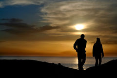 Silhouetted couple at sunset. Overlooking the ocean royalty free stock photos