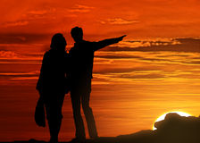 Silhouetted couple at sunset. Silhouetted newlywed couple walking on beach with sea and orange sunset background Royalty Free Stock Photos