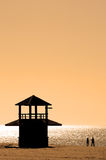 Silhouetted couple walking along beach at sunset. Couple in silhouette walking along sunny beach at sunset with dark watch tower Royalty Free Stock Image