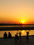 Silhouetted couple watching sunset. At Mekong river waterfront, Vientiane, Laos, Southeast Asia Royalty Free Stock Photography