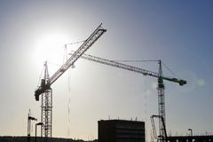 Silhouetted cranes. Bright sunshine behind construction site (with lens flare effect on right royalty free stock photography