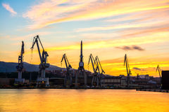Silhouetted cranes at shipyard,. Urban landscape of silhouetted cranes Royalty Free Stock Photos