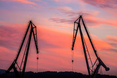 Silhouetted cranes at shipyard,. Urban landscape of silhouetted cranes Stock Photography