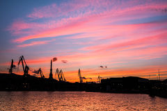 Silhouetted cranes at shipyard,. Urban landscape of silhouetted cranes Stock Image