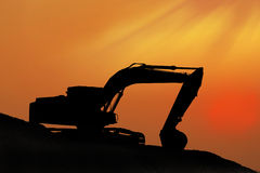 Silhouetted Digging Machine. And orange sky Stock Image