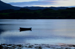 Silhouetted Dingy on Loch Dunvegan. Silhouetted boat on Loch Dunvegan on the Isle of Skye Stock Images