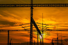 Silhouetted electric pylon with power line at sunset Stock Photo