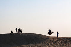 Silhouetted Family Group Couple on Camel desert landscape Stock Photos