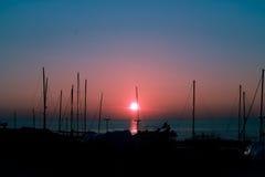 Silhouetted fartyg i en hamn på solnedgången Royaltyfri Fotografi