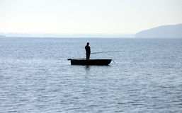 Silhouetted fisherman standing on a boat Stock Photography