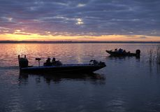 Silhouetted Fishermen Heading Out as the Sun Comes Up in a Beautiful Sunrise. Silhouetted Fisherman Head Out in Their Bass Boats as the Sun rises in a Beautiful royalty free stock image